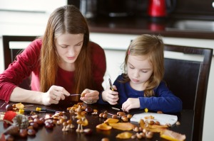 Mother and her kid making chestnuts creatures